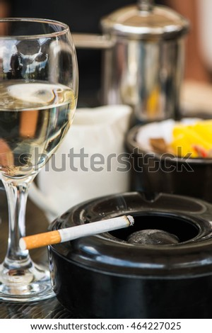 Glass of White Wine With an Ashtray and Cigarette on a Table In a Cafe or Restaurant