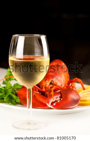 Glass of white wine with cooked lobster on the plate on black background - stock photo