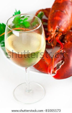 Glass of white wine with cooked lobster on the plate, top view - stock photo