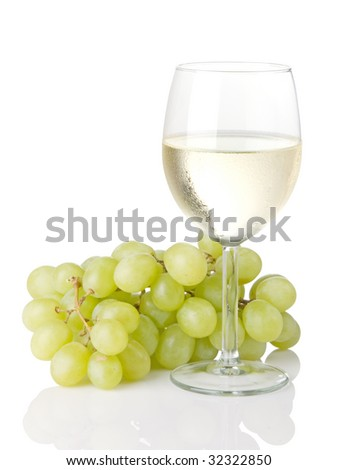 Glass of white wine with green grapes - stock photo
