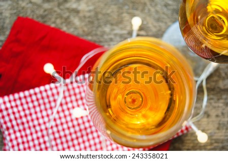Glass of white wine with lights on old wooden table - stock photo
