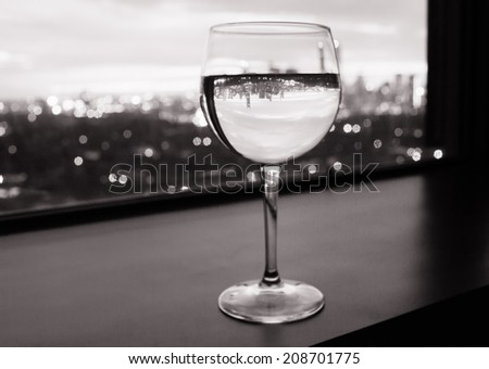Glass of wine against the city view. - stock photo