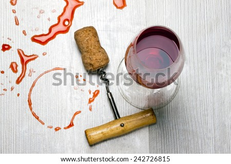 glass of wine and a corkscrew with cork from wine stains on the table - stock photo