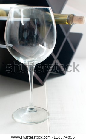 Glass of wine and bottle on the rack