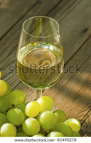 glass of wine and bunch of grapes on rustic wooden table