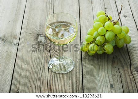 glass of wine and cluster of grapes on wood table