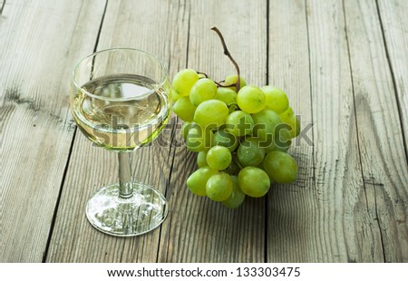 glass of wine and cluster of grapes on wood table - stock photo