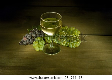 glass of wine and grapes on wooden - stock photo