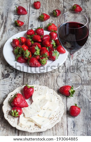 glass of wine, cheese and fresh strawberries on wooden table - stock photo