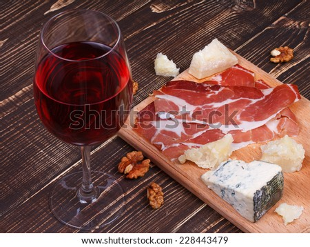 Glass of wine, cheese and prosciutto on wooden background - stock photo