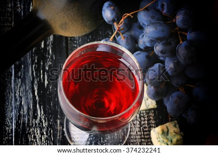 glass of wine grapes alcohol bottle cheese worn wooden background retro vintage style - stock photo