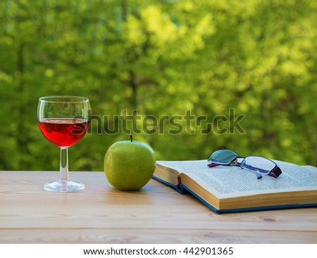 glass of wine green apple eyeglasses and book on table in the garden - stock photo