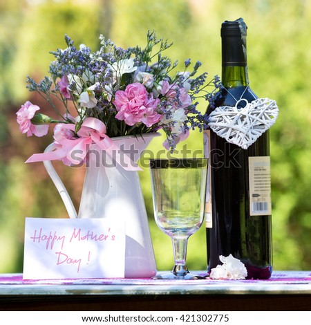 glass of  wine on a table in the garden on a sunny day - stock photo