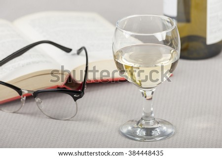 Glass of wine on a table with an open book and reading glasses - stock photo