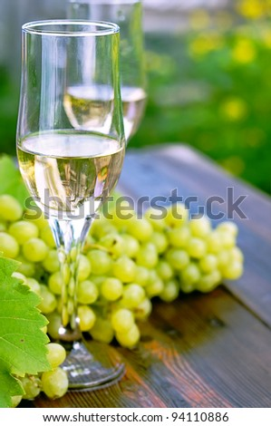 glass of wine on a wooden table. Bunches of grapes. - stock photo