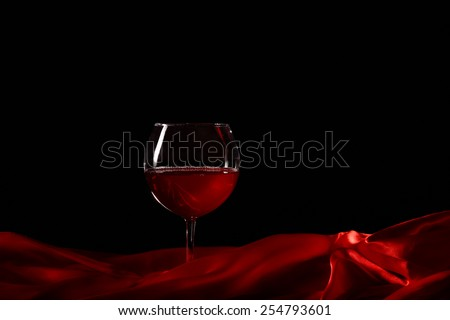 Glass of wine on red silk with dark background - stock photo