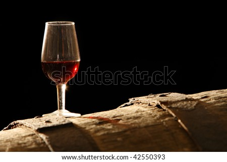 glass of wine stands on a barrel - stock photo