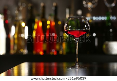 Glass of wine with bar on background - stock photo