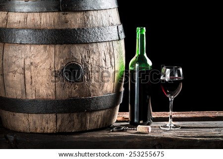 Glass of wine with bottle and old wooden barrel - stock photo