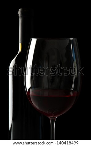 Glass of wine with bottle on black background - stock photo