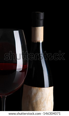 Glass of wine with bottle on bright background - stock photo