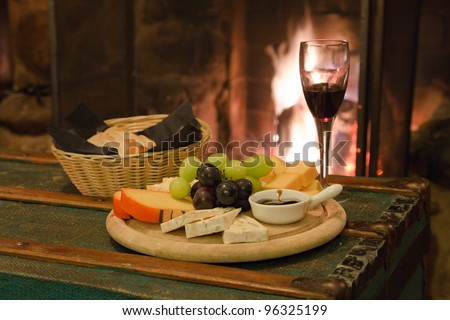 Glass of wine with bread cheese and grapes fire place in background - stock photo