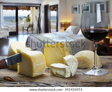 Glass of wine with cheese at the beach hotel room - stock photo