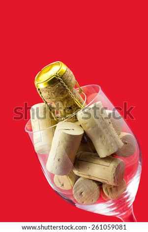 Glass of wine with cork stoppers on red background - stock photo