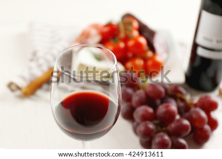 Glass of wine with food on table closeup - stock photo