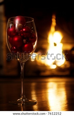 Glass of wine with red baubles in front of the fireplace.  Selective focus, golden glow from the fire. - stock photo