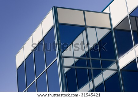 Glass Office Building and reflection, with a blue sky background.