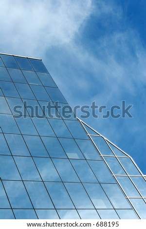 glass office building with reflection of blue sky