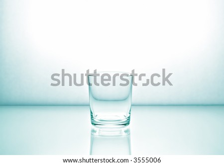 Glass on a light glossy surface. Light green toning. - stock photo