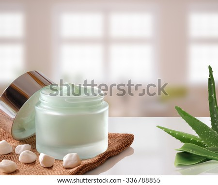 Glass open jar with facial or body cream aloe vera on burlap. With lid, small stones and aloe plant.Windows background. Front view. - stock photo