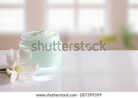 Glass open jar with facial or body cream on white table. with flower and background windows. Front view. - stock photo