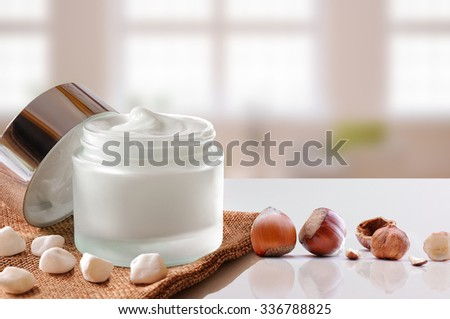 Glass open jar with facial or body hazelnuts moisturizer on burlap. With lid, small stones and hazelnuts.Windows background. Front view. - stock photo