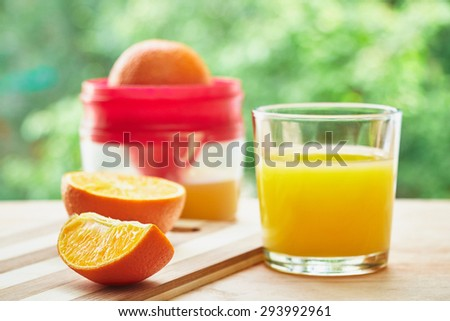 Glass, oranges and juicer on the wooden cutting board on green blurred background