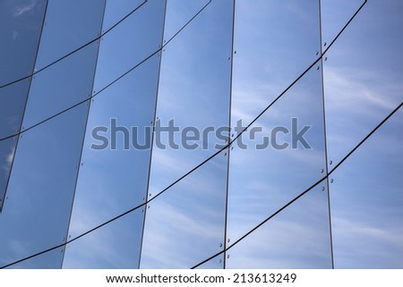 glass panes on curved facade of trade building reflecting blue sky and clouds - stock photo