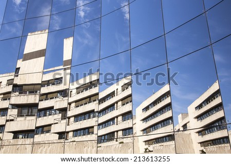 glass panes on facade of trade building reflecting blue sky and another building - stock photo