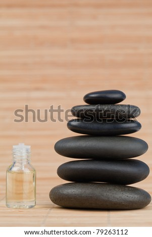 Glass phial filled in with pale yellow liquid and a stack of black pebbles against a bamboo background