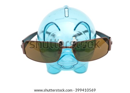 Glass piggy bank with sunglasses isolated on white
