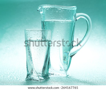 Glass pitcher and glass of water on blue background - stock photo