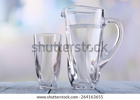 Glass pitcher and glass of water on wooden table on bright background - stock photo