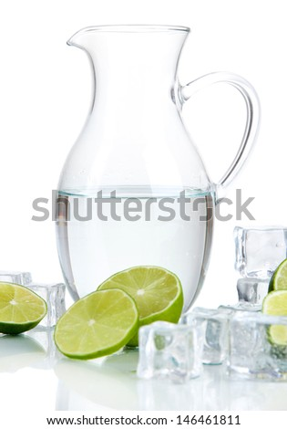 Glass pitcher of water with ice and lime isolated on white - stock photo