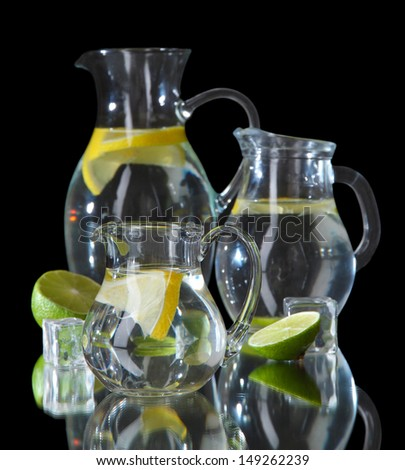 Glass pitchers of water isolated on black - stock photo