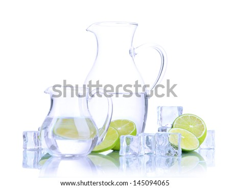 Glass pitchers of water with ice and lime isolated on white - stock photo