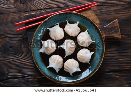 Glass plate with dim-sums in soy sauce, rustic wooden setting, top view - stock photo