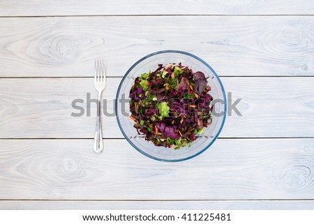 glass plate with salad on table - stock photo