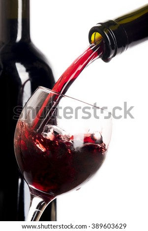 Glass poured with red wine and bottle with red wine isolated on white - stock photo