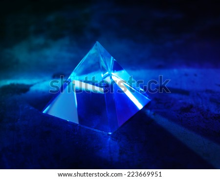 Glass prism with intensive light coming through. refractions of light in a glass prism. Focus is front edge. - stock photo